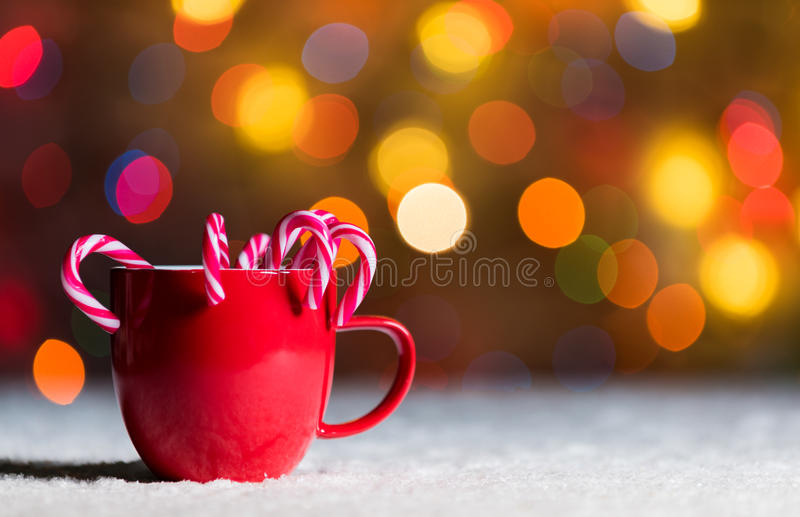 Red mug with candy canes in snow with defocussed fairy lights, bokeh in the background, Festive Christmas background. Red cup, red mug with candy canes in snow royalty free stock photos
