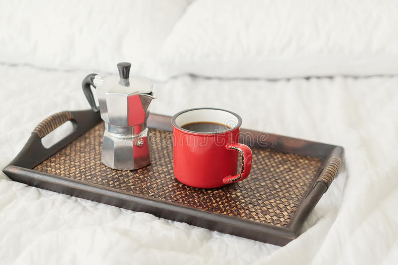 Red mug of coffee with steel coffee percolator on bed. Red metal mug of coffee with steel coffee percolator on wooden tray for breakfast on bed stock photos