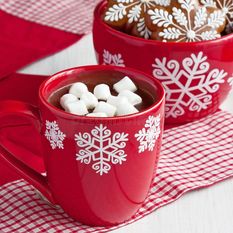Red mugs with hot chocolate and marshmallows and gingerbread cookies royalty free stock images