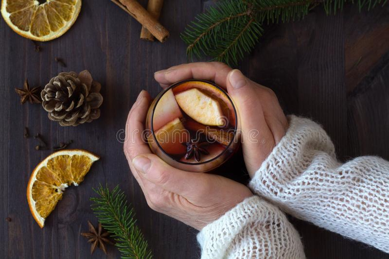 Woman`s hands holds hot mulled wine in a glass with orange and spices on wooden background. winter collection. top view royalty free stock images
