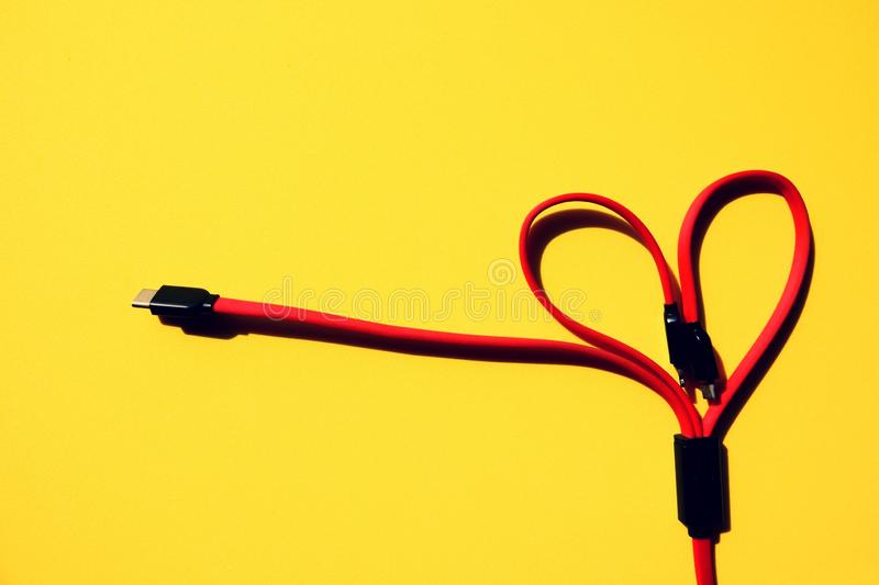 Red multi charger cable heart shape on yellow background royalty free stock image