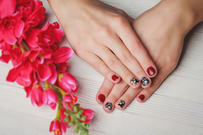 Red nail art with printed flowers on wooden background stock photo