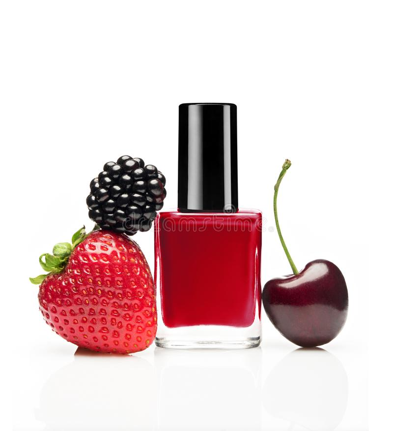 Red nail polish bottle with berries. Blackberry, strawberry, cherry on white background royalty free stock images