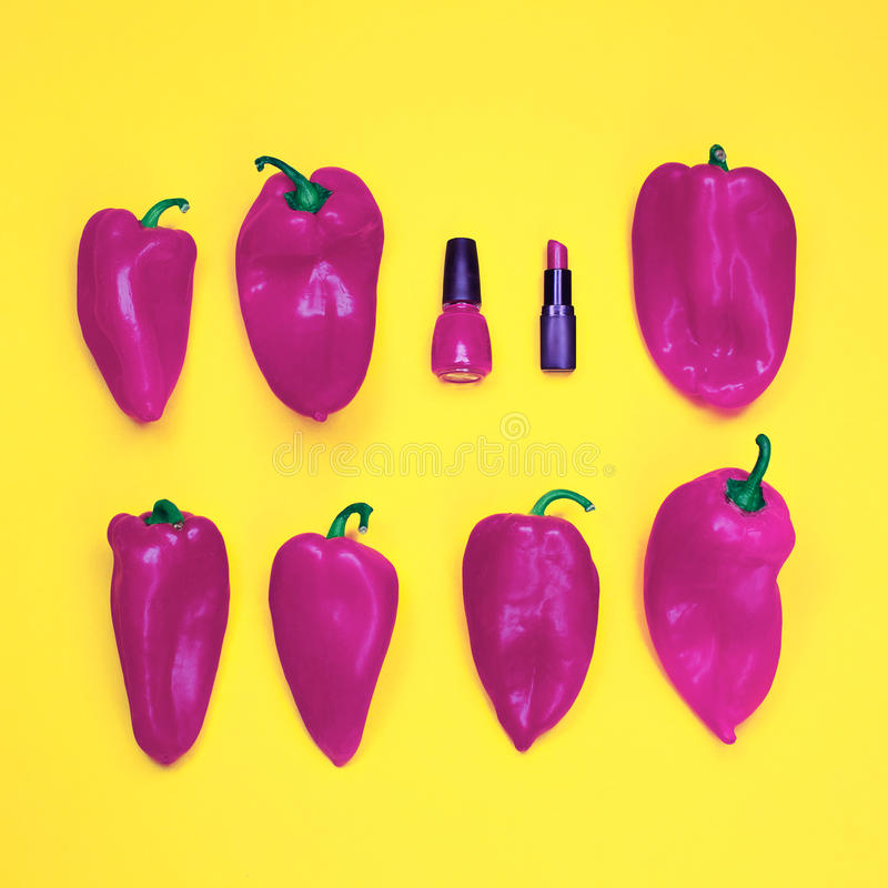 Red nail polish and lipstick, among a large number of red peppers on yellow background. Conceptual photography. red nail polish and lipstick, among a large stock images
