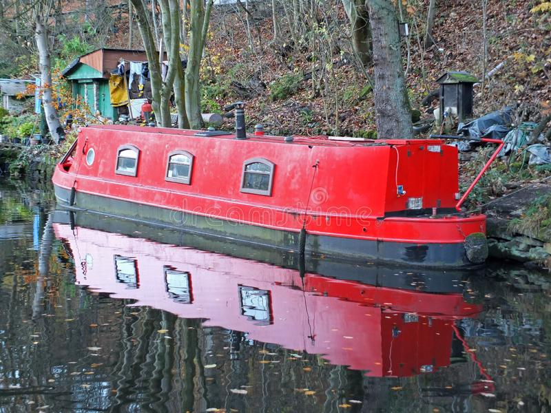 Red narrow boat reflected in still water on the rochdale canal in hebden bridge surrounded by autumn trees and sheds stock photos