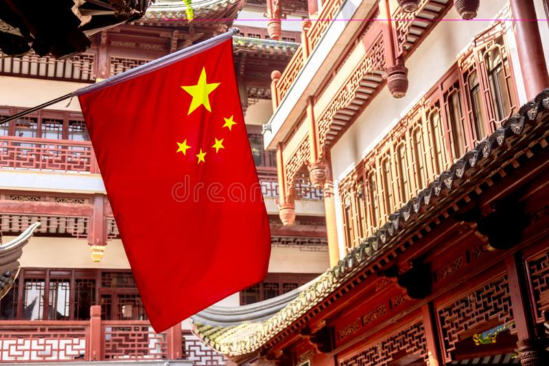 Red national flag of China against old chinese buildings at Yuyuan Garden in Shanghai, China.  royalty free stock images