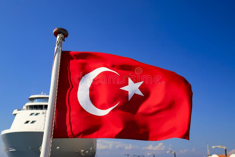 Red National Flag of Turkey with a half month and a star against the sky and a ocean liner, Turkish state symbol, autumn, spring, stock photo