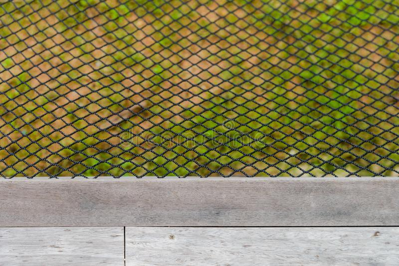 Red negra de la hamaca del color cerca del piso de madera imagenes de archivo