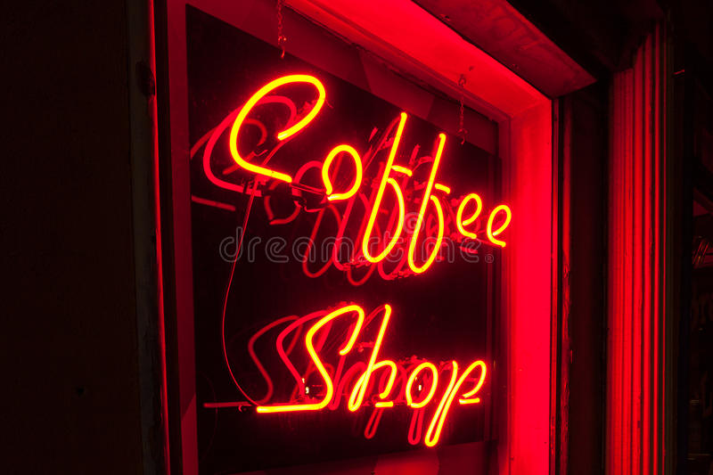 Red Neon Coffee Shop sign left side version closer. Coffee Shop sign in red neon lighting on a black background at an angle. Also available in a straight-on royalty free stock image