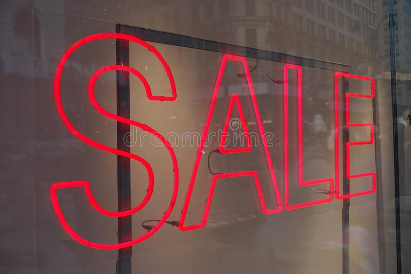 Red Neon Sale Sign in a Store Window. A Red Neon Sale Sign in a Store Window with Reflections of the City royalty free stock image