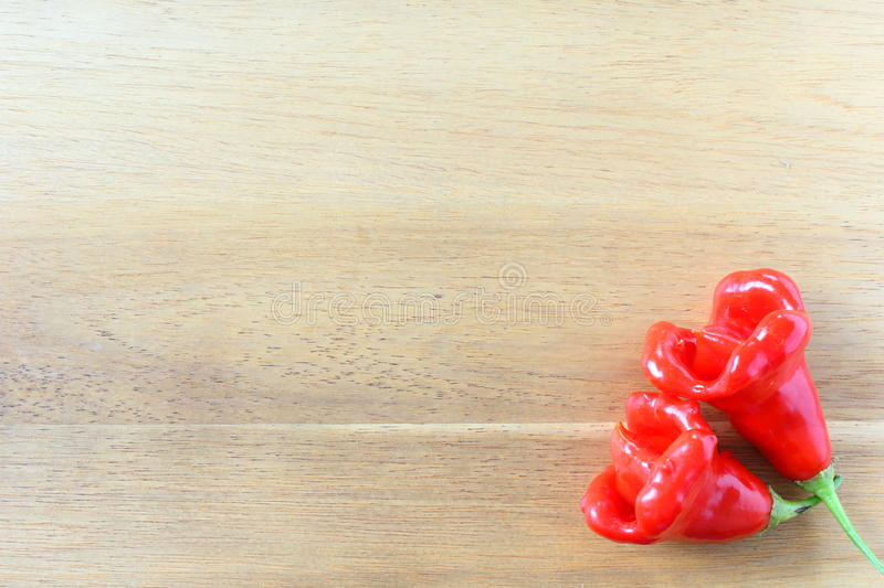 Red nepalese bell chili peppers on a wooden board. Composition of red nepalese bell chili peppers on a wooden board royalty free stock image