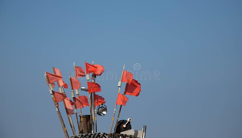 Red net marker flags on a traditional fishing boat, copy space royalty free stock photography