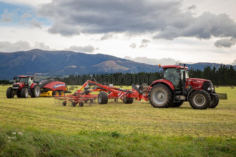 Red New Holland tractors work mowing, raking and baling hay stock images