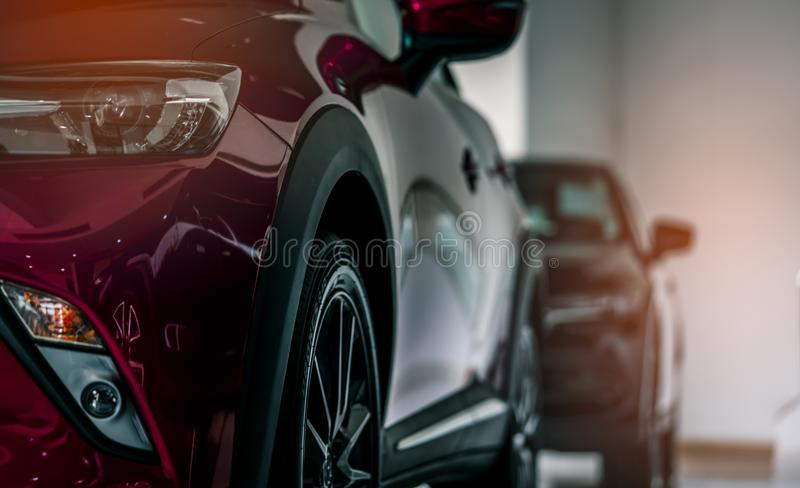 Red new luxury SUV compact car parked in modern showroom for sale. Car dealership office. Car retail shop. Electric car technology royalty free stock photography