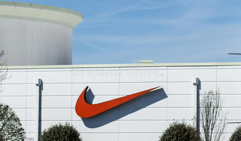 Red Nike swoosh logo on outside of store. Deer Park, New York, USA - 17 April 2019: A large Nike swoosh in on the outside of the Nike Store facing the road on a royalty free stock photos