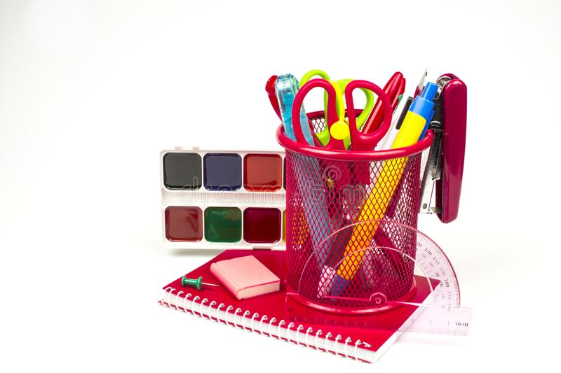The notepad of red color, a glass with pens and scissors, watercolor paints, eraser, isolated on a white background. The  red notebook, a glass with pens and royalty free stock image
