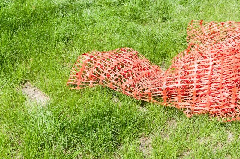 Red o cerca anaranjada de seguridad de la construcción, usada como barrera protectora de la precaución, en la hierba verde fotos de archivo libres de regalías
