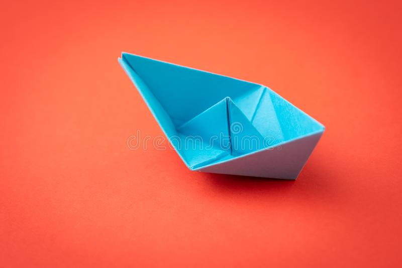 Red ocean business competition, survive success or winner company metaphor concept, blue origami paper ship on red background as stock photography