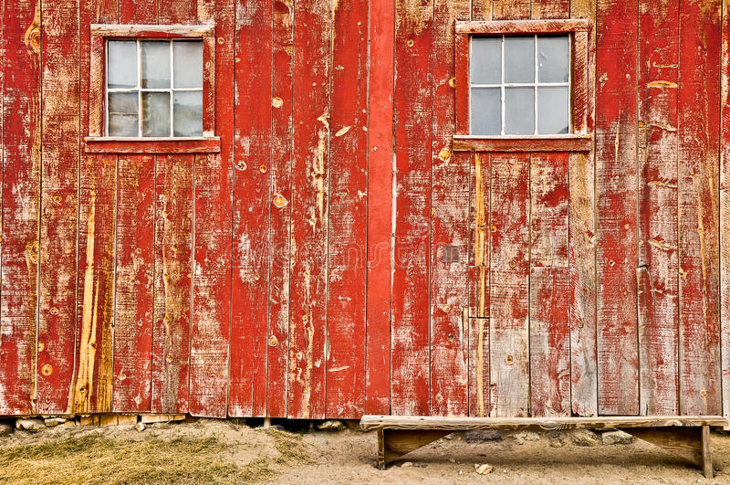 Red old barn windows and lonely bench. Red old barn with two windows and lonely bench, no sky and no horizon royalty free stock images