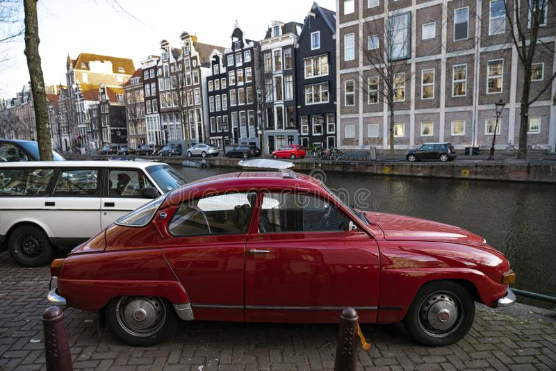 Red old car in Canals of Amsterdam Holland. Amsterdam Holland The city of Amsterdam, capital of the Netherlands, is built on a network of artificial canals in stock image