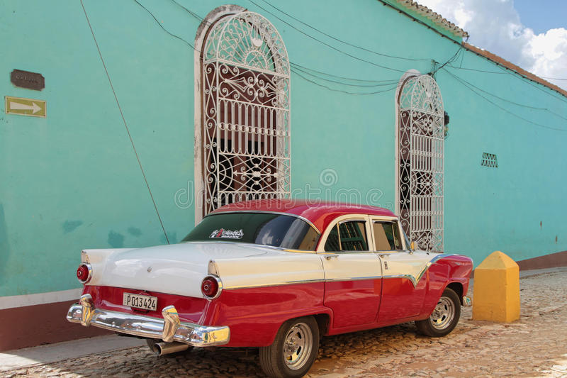 Red old car on green wall in Trinidad royalty free stock photo