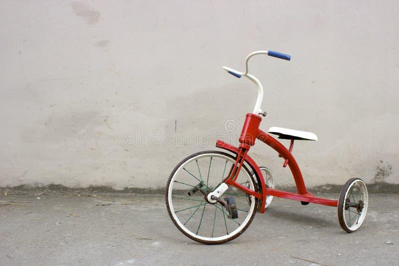 Red Old Children's Bike in a Poor Neighborhood. Red Old Fashion Antique Children's Bike in a Poor Neighborhood in front of a Grey Wall. Old Kids' Tricycle stock photos