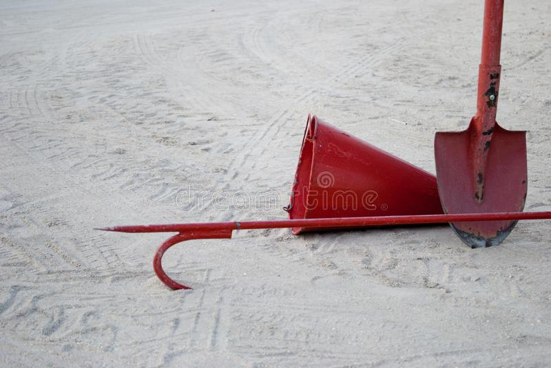 Red fireman scrap hook, spade, cone bucket shield against the background of sand. Red old fire scrap scrap, fire cone bucket, bayonet shovel, extinguishing of royalty free stock images