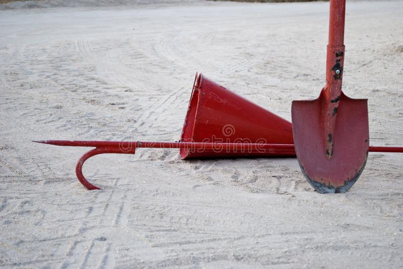 Red fireman scrap hook, spade, cone bucket shield against the background of sand. Red old fire scrap scrap, fire cone bucket, bayonet shovel, extinguishing of stock photography