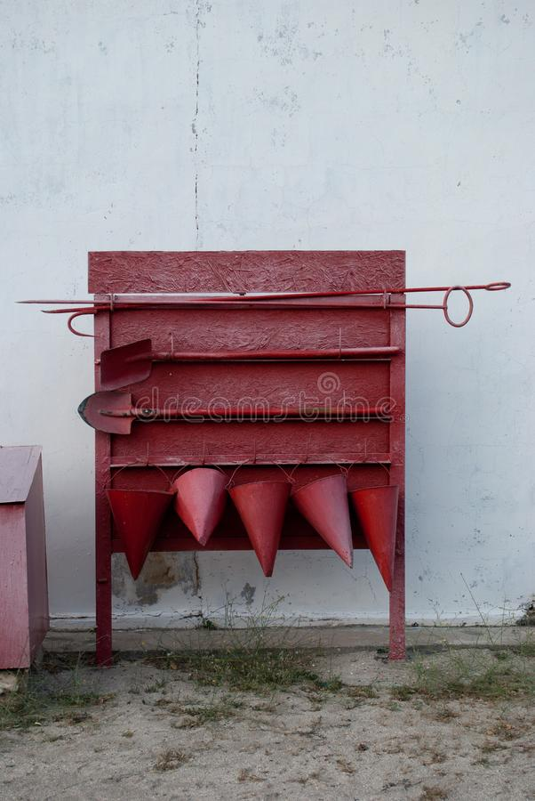 Red fire shield against a white wall background. Red old fire shield against the white wall, screech, scrap, five fire cone buckets, two shovels - bayonet and royalty free stock photos