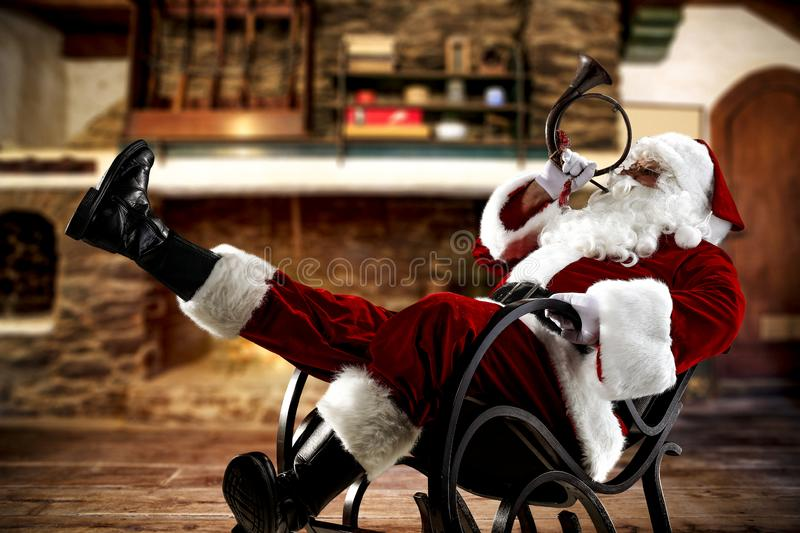 Red old Santa Claus with long beard in red clothes. Santa with trumpet horn  on rocking chair. Red old santa claus in red clothes.  Chrsitmas time and cold royalty free stock photo