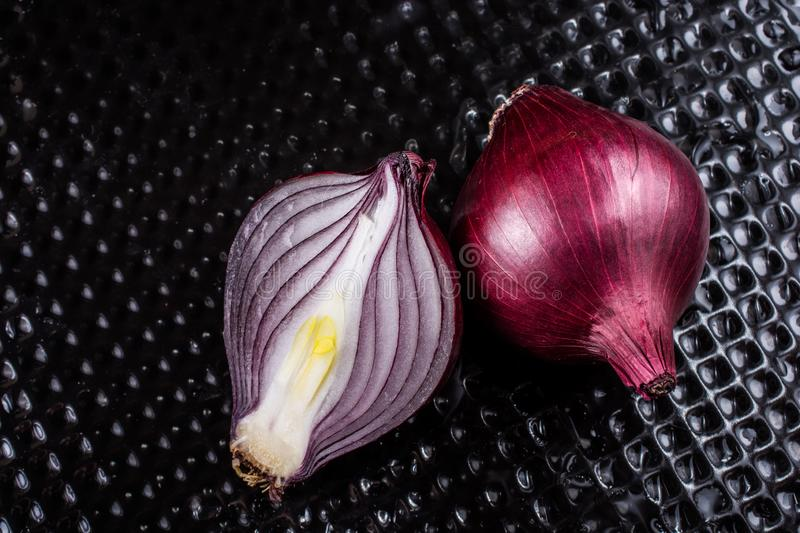 Red onion bulb cut in half on certain  background stock images