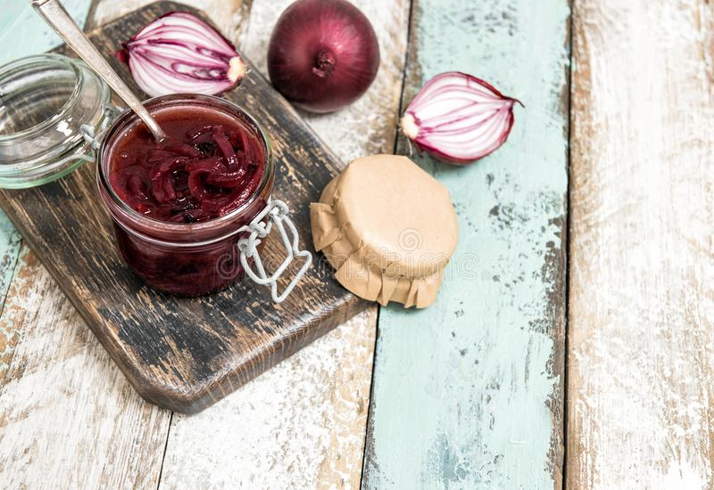 Red onion marmalade in jar Vegetable jam. Red onion marmalade in jar. Vegetable jam on rustic wooden background. Preserving ingredients royalty free stock photos