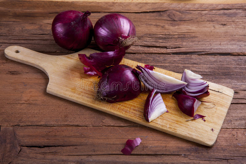 Red onions. Onions chopped on a chopping board shot at an angle on wood stock photo