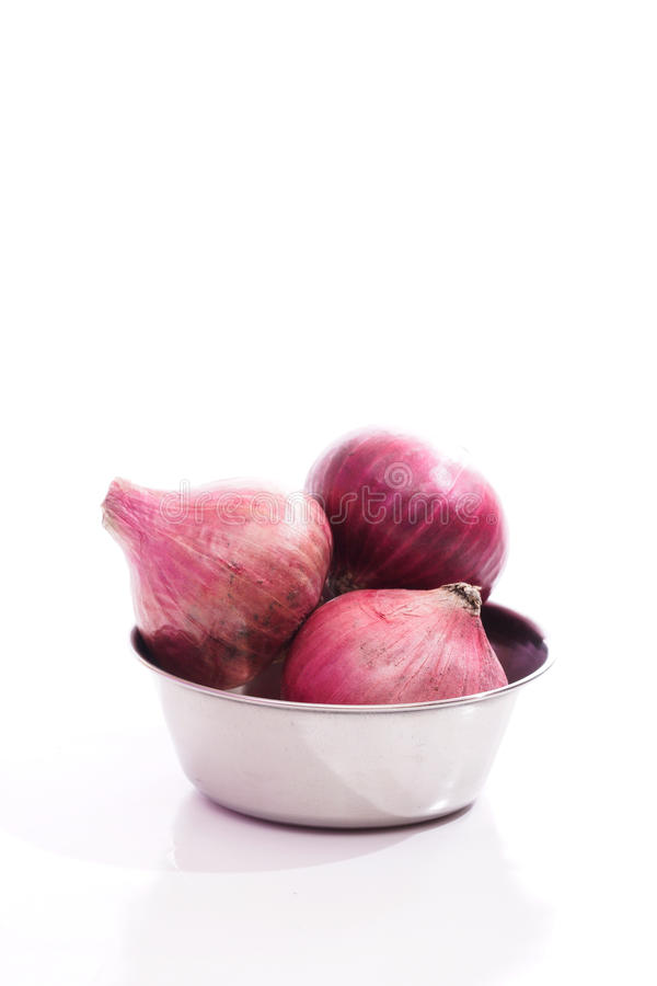 Red onions in a steel bowl over white background stock photos