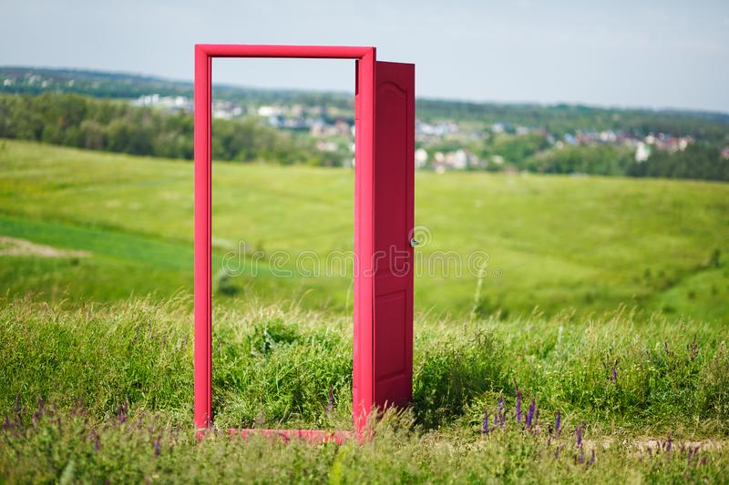 Red, open door in the field.  royalty free stock photography