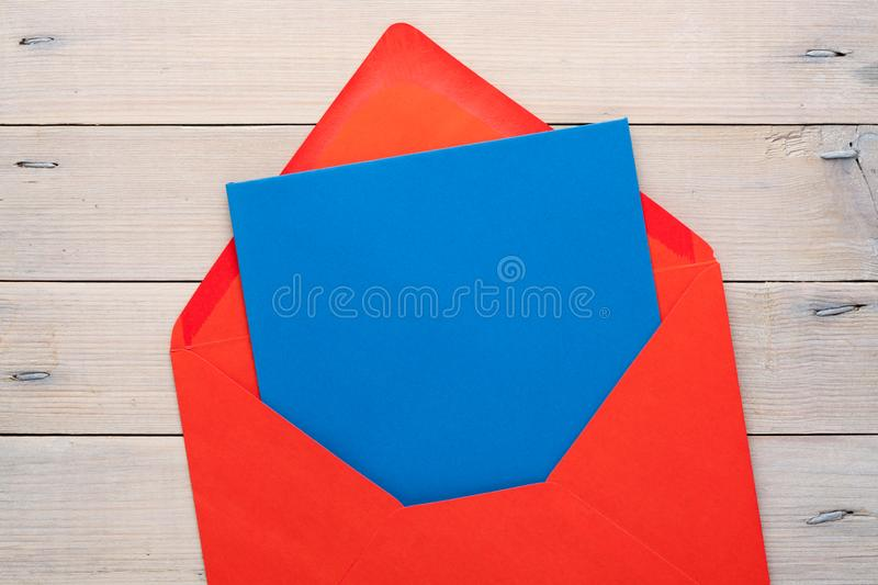 Blank Letter with Envelope. Red open envelope with a blue blank letter inside on a wooden background. Empty space stock images