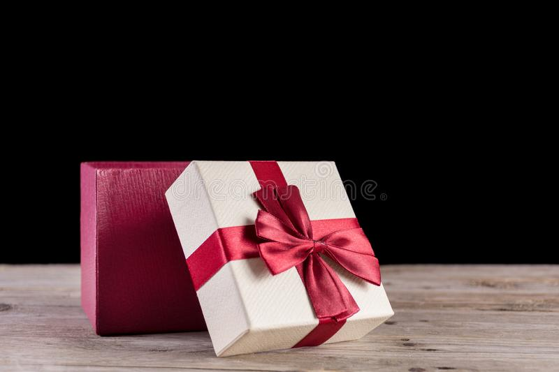 Red opened gift box with bow on retro wooden desk royalty free stock photos
