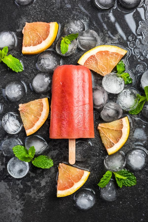 Red orange juice homemade popsicle over ice. Red orange homemade popsicle over ice, mint and fresh fruits background cold colorful concept cool copyspace dark royalty free stock images