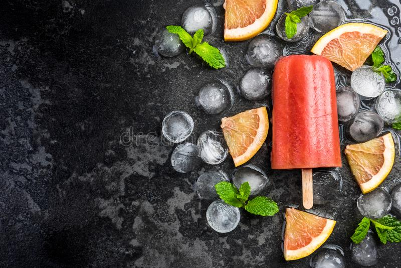 Red orange juice homemade popsicle over ice. Red orange homemade popsicle over ice, mint and fresh fruits background cold colorful concept cool copyspace dark stock images