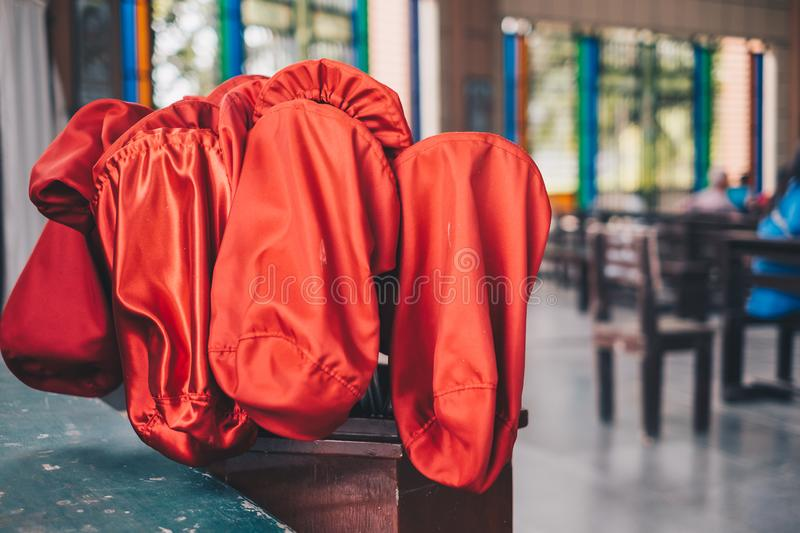Red orange offertory bags at the back of the church. royalty free stock image