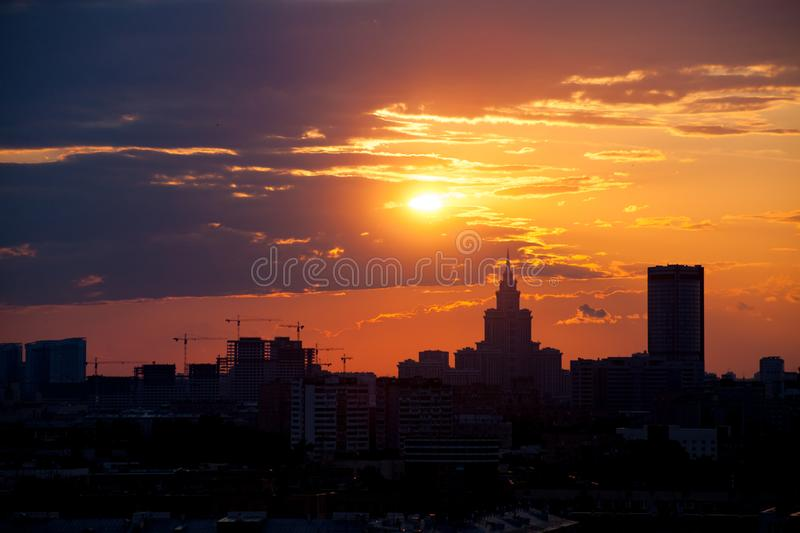 Red and orange sky with clouds and silhouette of cranes, construction and a skyscraper. Moscow stock image