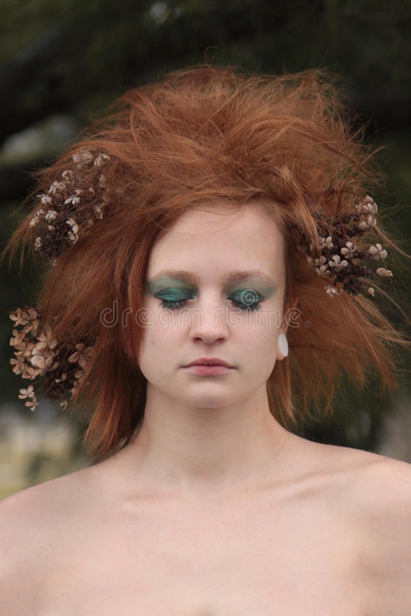 Red Orange Teased Hair with Dead Flowers. A woman with green eye make up and dead flowers in her hair stock photography
