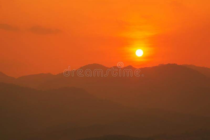 Red and orange warm sunlight in the sky during sunset with mountain range in foreground, shade and shadow, sunset sunrise. From Mae Hong Son province Thailand stock image