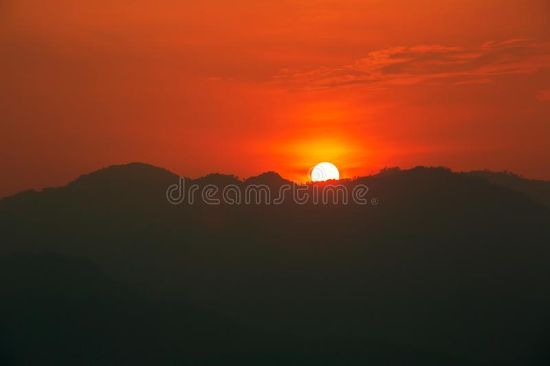 Red and orange warm sunlight in the sky during sunset with mountain range in foreground, shade and shadow, sunset sunrise. From Mae Hong Son province Thailand royalty free stock photo