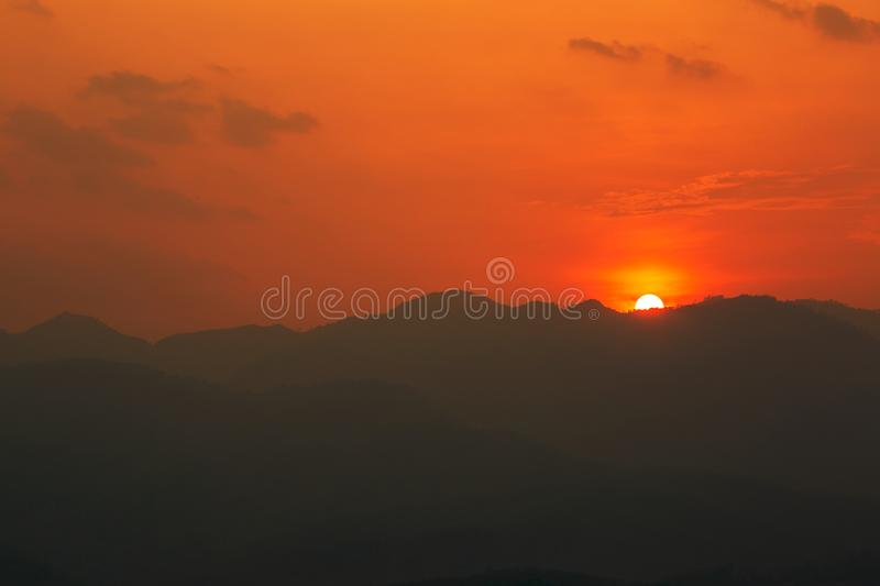 Red and orange warm sunlight in the sky during sunset with mountain range in foreground, shade and shadow, sunset sunrise. From Mae Hong Son province Thailand royalty free stock image