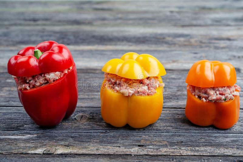 Red,orange and yellow filled pepper. On wooden ground stock photo