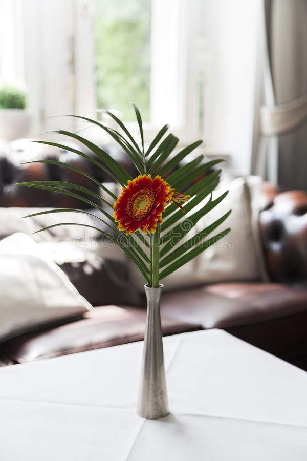 Red orange yellow gerbera flower with green palm leaf in metal vase on table stock photos
