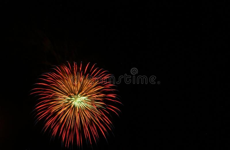 Red, orange, and yellow starburst firework on the Fourth of July royalty free stock images