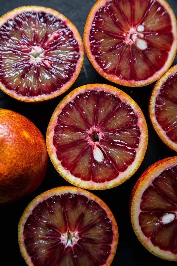 Red oranges on a dark background. Cut in half red oranges on a dark background stock photo