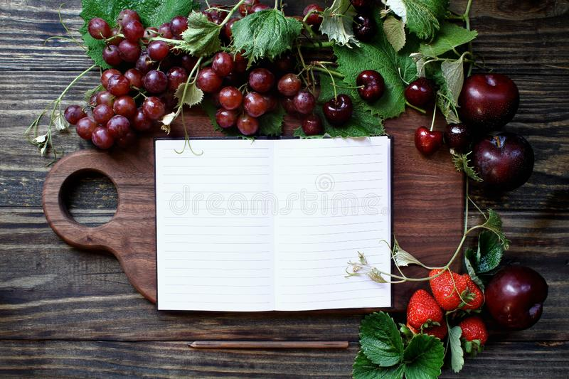 Red Organic Homegrown Fruit and Cutting Board with Cookbook royalty free stock images